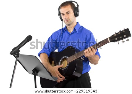 male singer holding a guitar and wearing headphones on white background