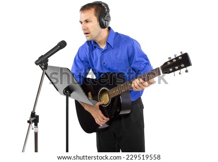 male singer holding a guitar and wearing headphones on white background - stock photo