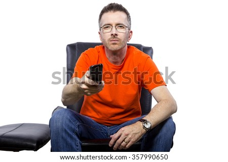 Male sitting indoors watching TV from the front view with a remote control - stock photo