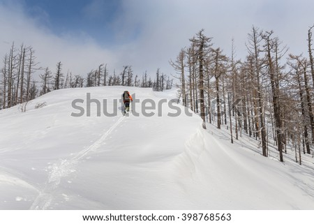Male skier hiking with backpack in winter mountains and forest