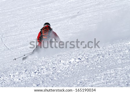 Male skier is carving on piste