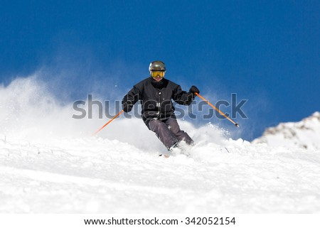 Male skier skiing in fresh snow on ski slope on a sunny winter day at the ski resort Soelden in Austria. - stock photo