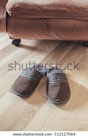 Male slippers in front of the chair