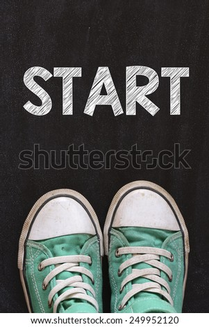 Male sneakers and word start. Male sneakers on the asphalt road with drawn word start - stock photo