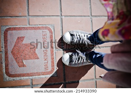 Male sneakers on the asphalt road with drawn direction arrow... - stock photo