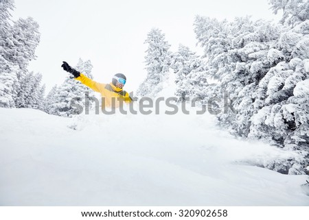 Male snowboarder having fun in deep backcountry powder snow during winter blizzard in Alps - extreme sports concept - stock photo