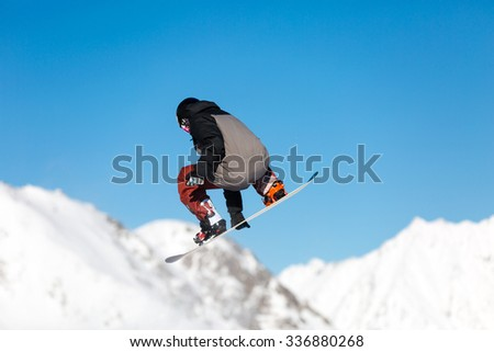 Male snowboarder performing a jump in a snowpark with snowy mountains in the background. - stock photo