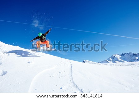 Male snowboarder wearing green helmet, black jacket and orange pants having fun jumping against blue sky on ski resort piste - winter sports concept - stock photo