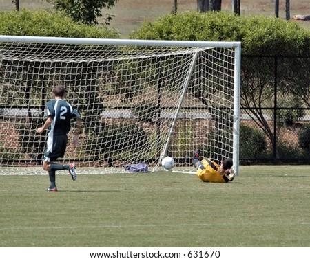 Male soccer goal keeper misses the shot - stock photo