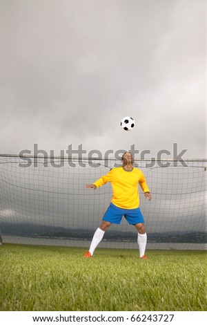 Male soccer goalie hitting ball with head - stock photo