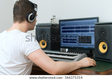 Male sound producer working in recording studio. - stock photo