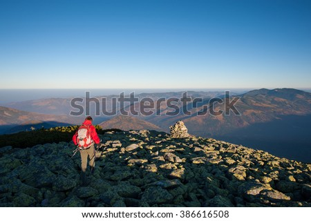 Male sportsman backpacker walking on the rocky top of the mountain with beautiful mountains on background. Man is wearing red jacket and has trekking sticks and backpack on. Rear view. - stock photo