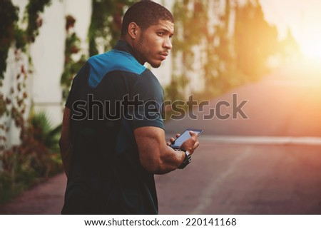 Male sportsman walking on the road to sunset holding phone in the hands, athletic build male runner holding mobile phone, attractive jogger using smart phone after self training outdoors - stock photo