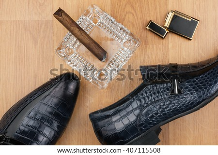 Male still life, classic men's shoes and a cigar in an ashtray, can use as background - stock photo