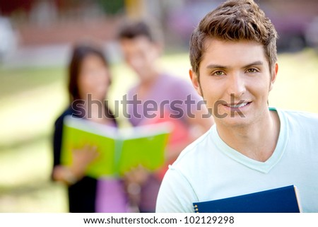 Male student carrying notebooks outdoors and smiling - stock photo