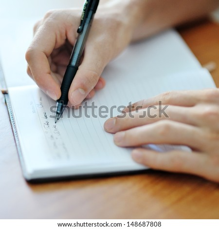 male student hand with a black pen writing on a white notebook - stock photo
