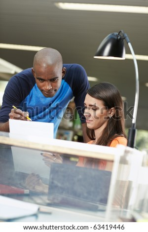 male student helping her mate with homeworks in library. Vertical shape, front view, waist up, copy space