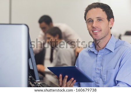 Male student holding a tablet sitting in front of computer in computer class - stock photo