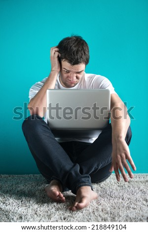 male student holding laptop working problem using laptop looking at screen,  - stock photo