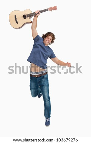 Male student jumping with his guitar against white background