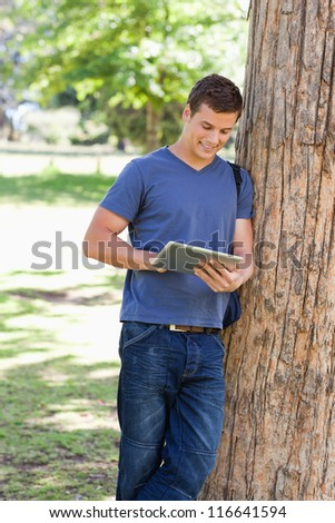 male student leaning against a tree while using a touch pad in a park - stock photo