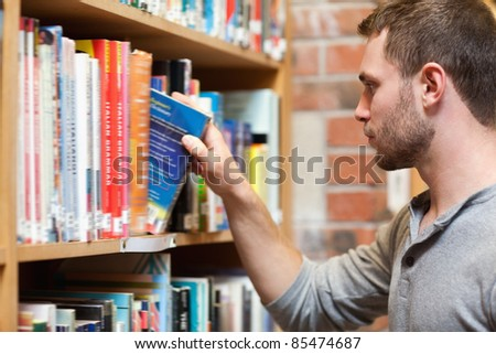 Male student picking a book in a library - stock photo