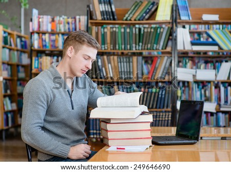 male student reading book in library