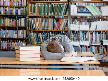 Male student sleeping in library - stock photo