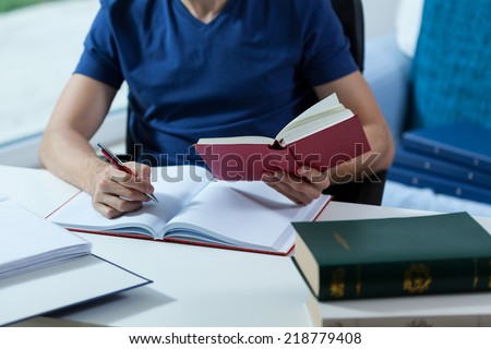 Male student transcribing the notes from the book in library - stock photo