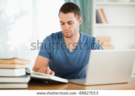 Male student using his laptop for his homework - stock photo