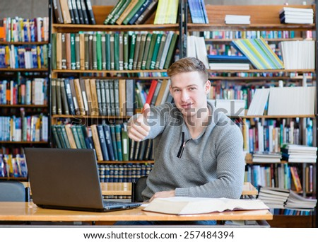 Male student with laptop showing thumbs up in the university library