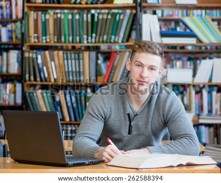Male student with laptop studying in the university library