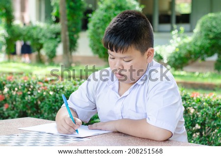 Male Student Working At Desk In  School. - stock photo