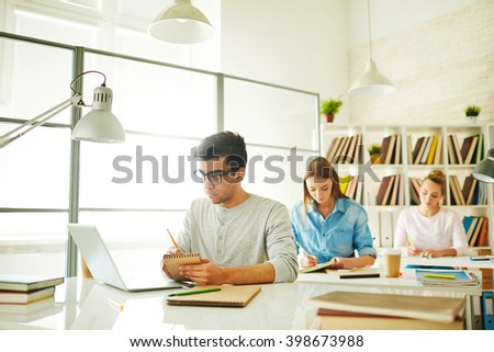 Male student working with his laptop at the table with women behind - stock photo