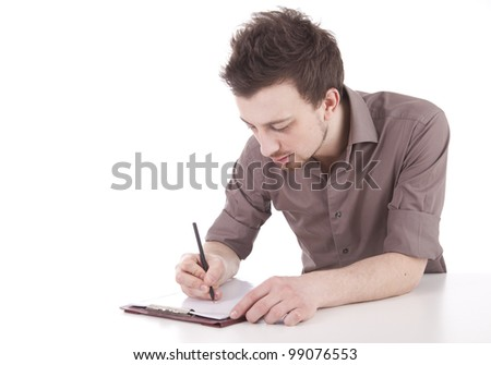 male student writing on clipboard, sitting at desk, white background