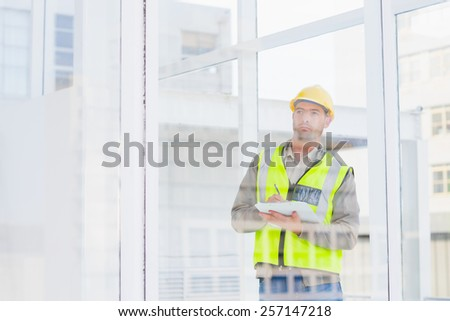 Male supervisor in reflective clothing writing on clipboard in office - stock photo