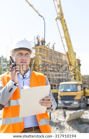 Male supervisor using walkie-talkie while holding clipboard at construction site - stock photo