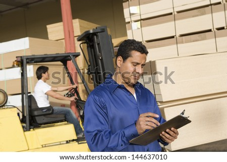 Male supervisor with clipboard and forklift truck driver in the background - stock photo