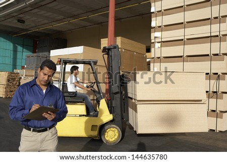 Male supervisor with clipboard in front of forklift stacking boxes at warehouse - stock photo