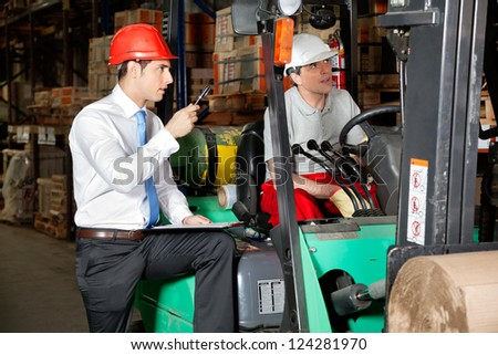 Male supervisor with clipboard instructing forklift driver at warehouse - stock photo