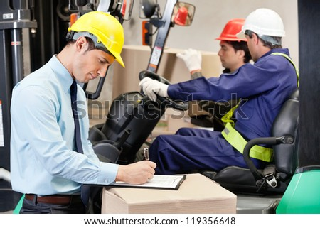 Male supervisor writing on clipboard with foremen driving a forklift at warehouse - stock photo