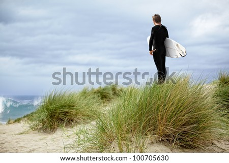 Male Surfer At The Beach, Standing In Green Sea Grass Sand Dunes On The Coast Of California ~ Boy On Vacation With Surf Board ~ Pacific Ocean Athletic Sport - stock photo