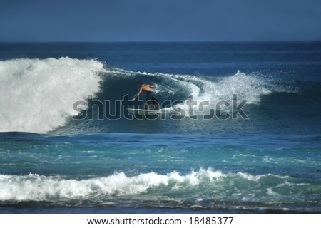 Male surfer reaches out to touch the curl as he is surfing off the shores of Kauai, Hawaii. - stock photo