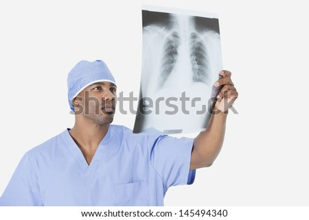 Male surgeon analyzing x-ray report over gray background - stock photo