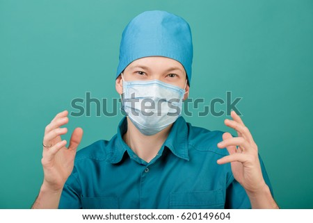 male surgeon in mask looking at camera on blue background, close up