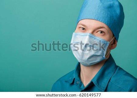 male surgeon in mask looking at camera on blue background, close up. copy space