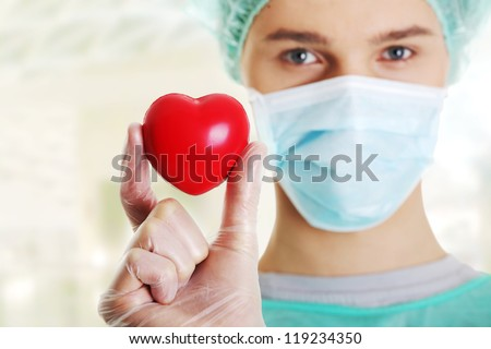 Male surgeon looking at camera at hospital and holding red heart, close up shot