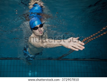 Male swimmer at the swimming pool. Underwater photo. - stock photo