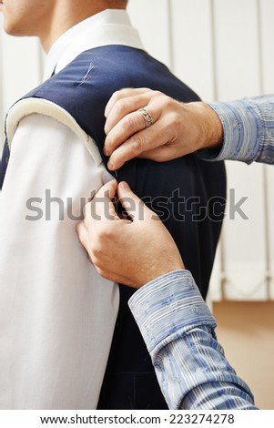 male tailor designer make marks on a jacket during bespoke suit fitting - stock photo