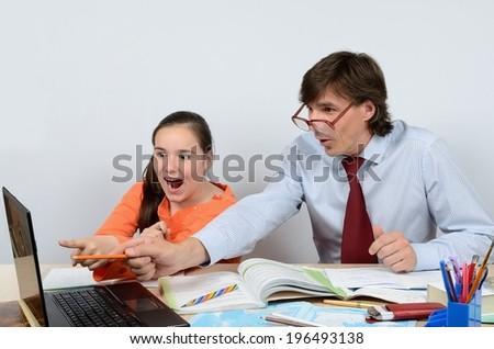 Male teacher fun teaches the schoolgirl to work on the computer - stock photo